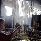 Una donna scatta delle foto in un mercato di Donetsk, distrutto negli scontri tra esercito ucraino e ribelli filorussi. (Philippe Desmazes, Afp)